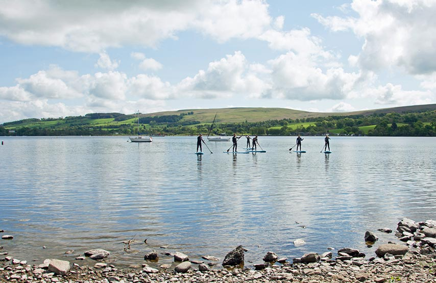 A group of stand up paddleboarders on the lake