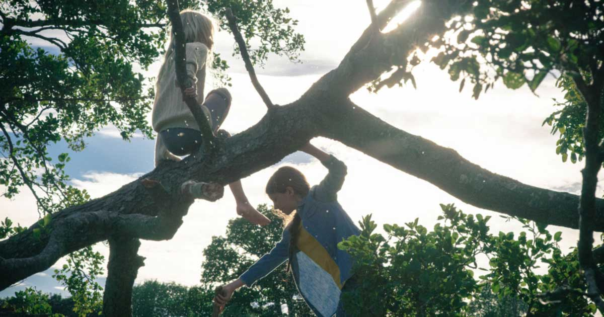 Two young girls tree climbing in the grounds at Another Place, a new hotel in the Lake District