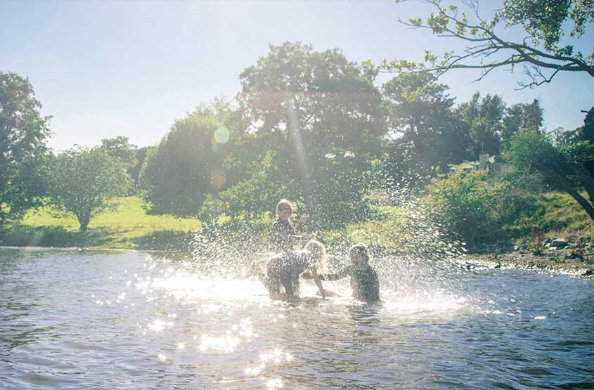 Children splashing about in Ullswater during their stay at the family-friendly hotel, Another Place, The Lake