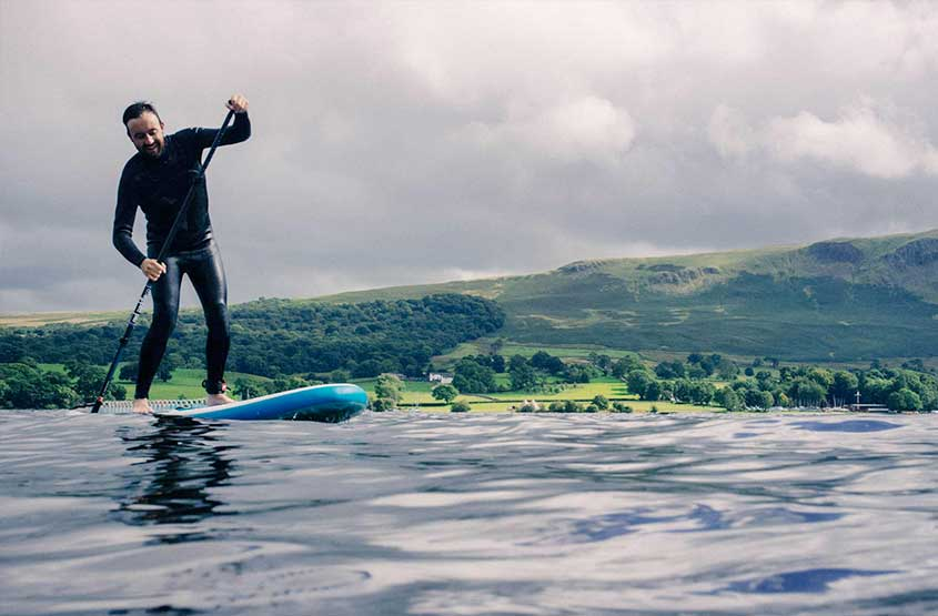 Man stand up paddling on Ullswater during a hotel stay at Another Place, The Lake