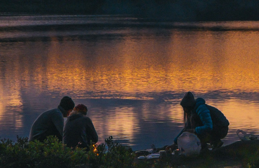 Group of friends enjoying a BBQ at sunset on the shores of Ullswater
