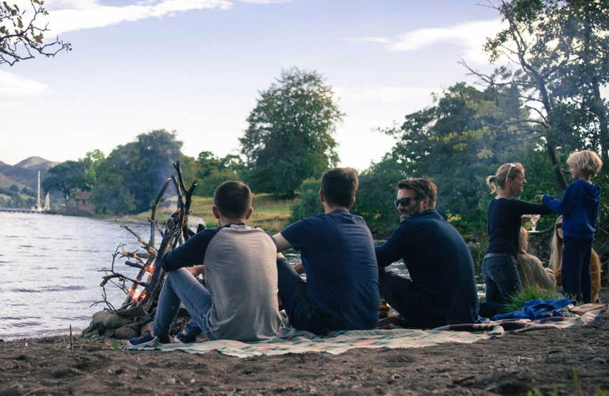 Group of friends sitting on blankets by a bonfire on the shores of Ullswater at Another Place, The Lake