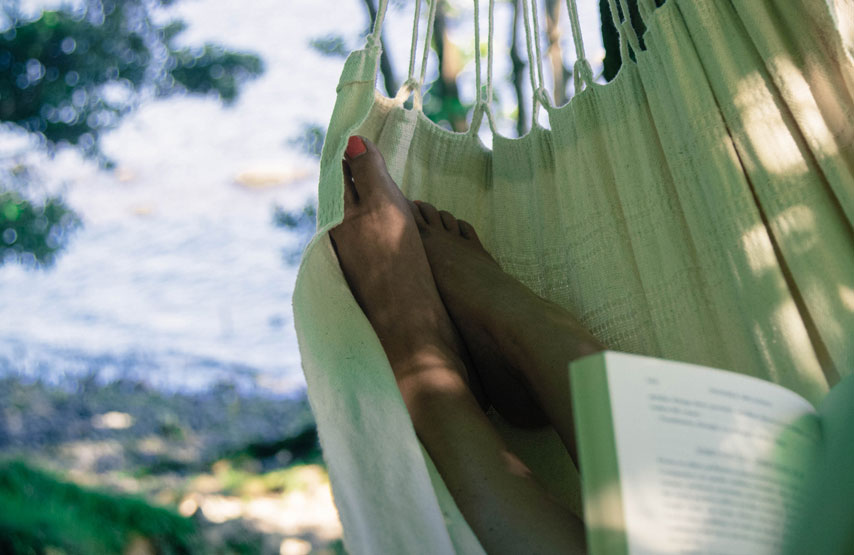 Relaxing in a hammock, reading a book during a hotel stay Another Place on the shores of Ullswater