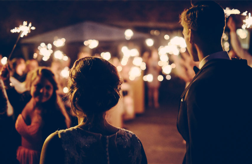 A couple walking through friends holding sparklers on their wedding day at Another Place, The Lake