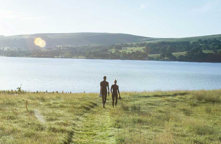 Couple going for a morning swim in Ullswater during their hotel stay at Another Place, The Lake