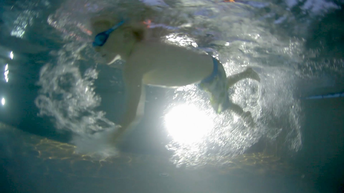 Underwater view of a young boy swimming in the pool in Swim Club at Another Place