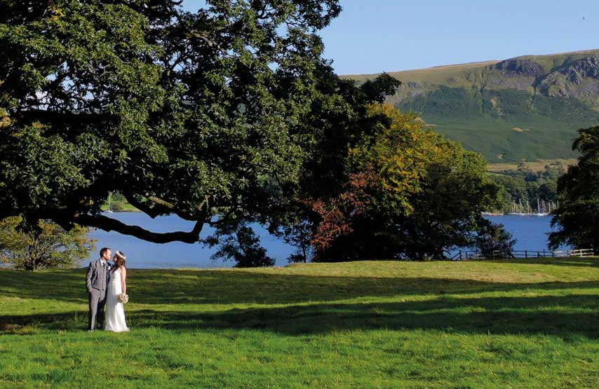 A wedding couple standing beneath a big tree at Another Place, a new hotel wedding venue on the shores of Ullswater