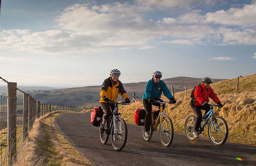 Three cyclists riding on quiet roads in the Lake District