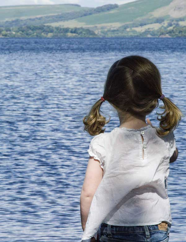 Little girl standing on the shores of Ullswater