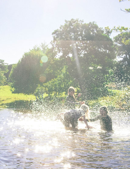 Children splashing about in Ullswater during their family hotel break at Another Place in the Lake District