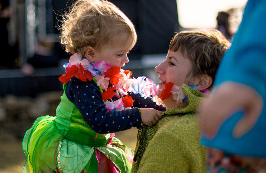 Mother and daughter playing with flower garlands at Solfest - a Lake District music festival