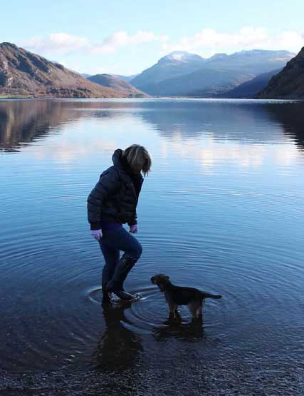 Owner paddling with their border terrier on the shore of Ullswater in the Lake District