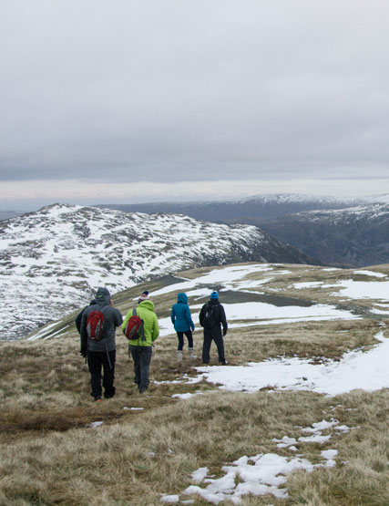 Group of friends exploring the snow-covered Lake District fells in winter