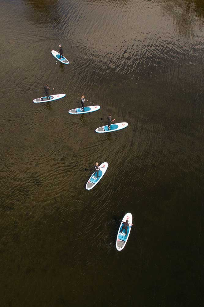 A group of people stand up paddling on Ullswater