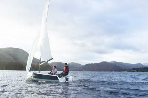 2 young people sailing on Ullswater with the fells in the background