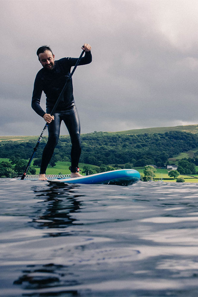 Man stand up paddling on Ullswater in the Lake District
