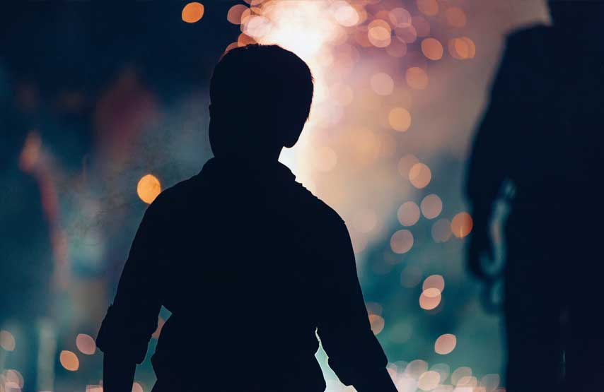 Young boy watching a bonfire at a gathering at Another Place, The Lake
