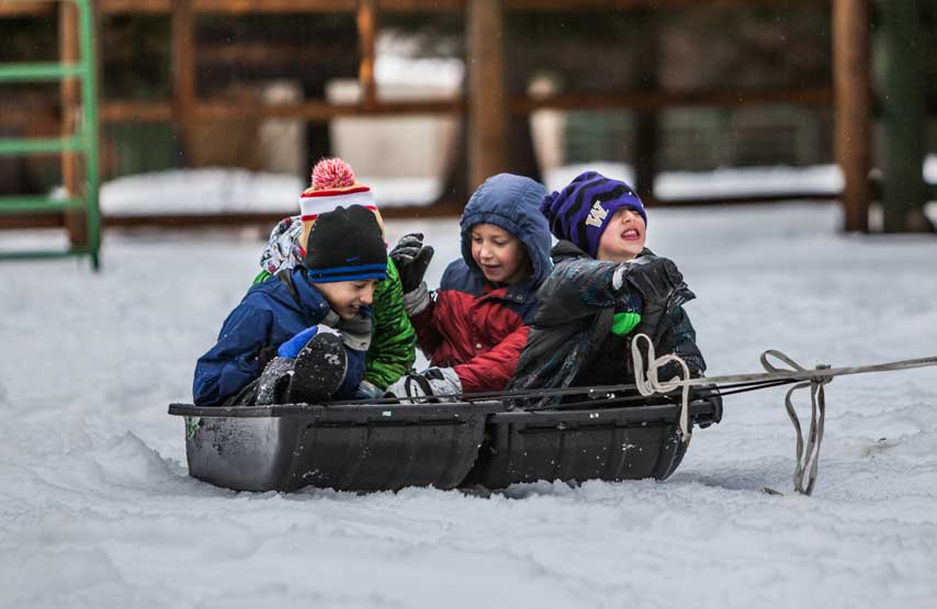 Group of children sledging in the snow at Another Place, The Lake