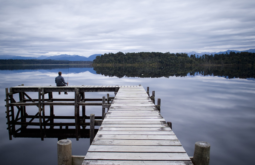 Man sitting on the jetty fishing with the Lake District fells in the background