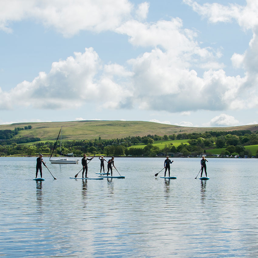 Group of people stand up paddling on Ullswater in the Lake District