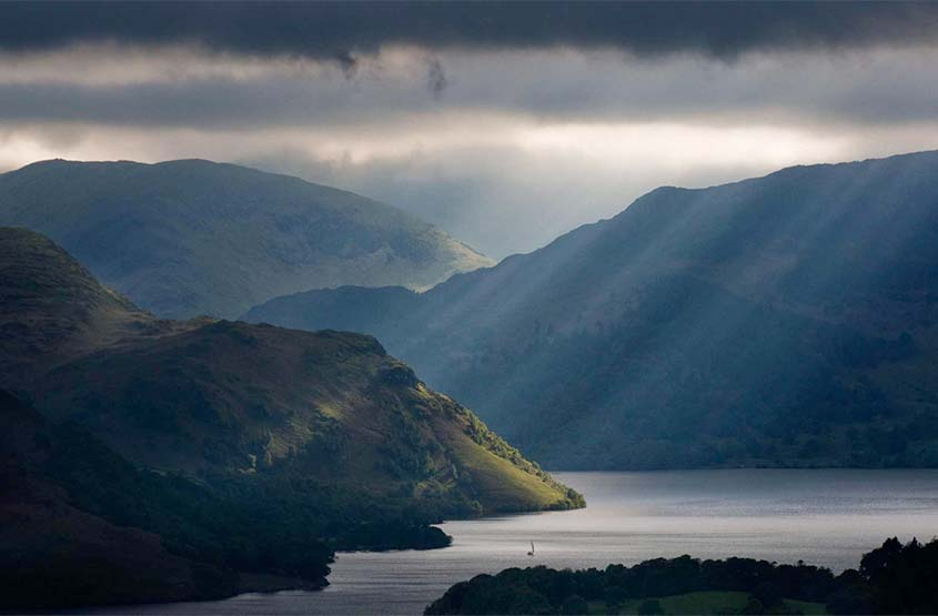 Rays of light breaking through the clouds and shining down on Ullswater