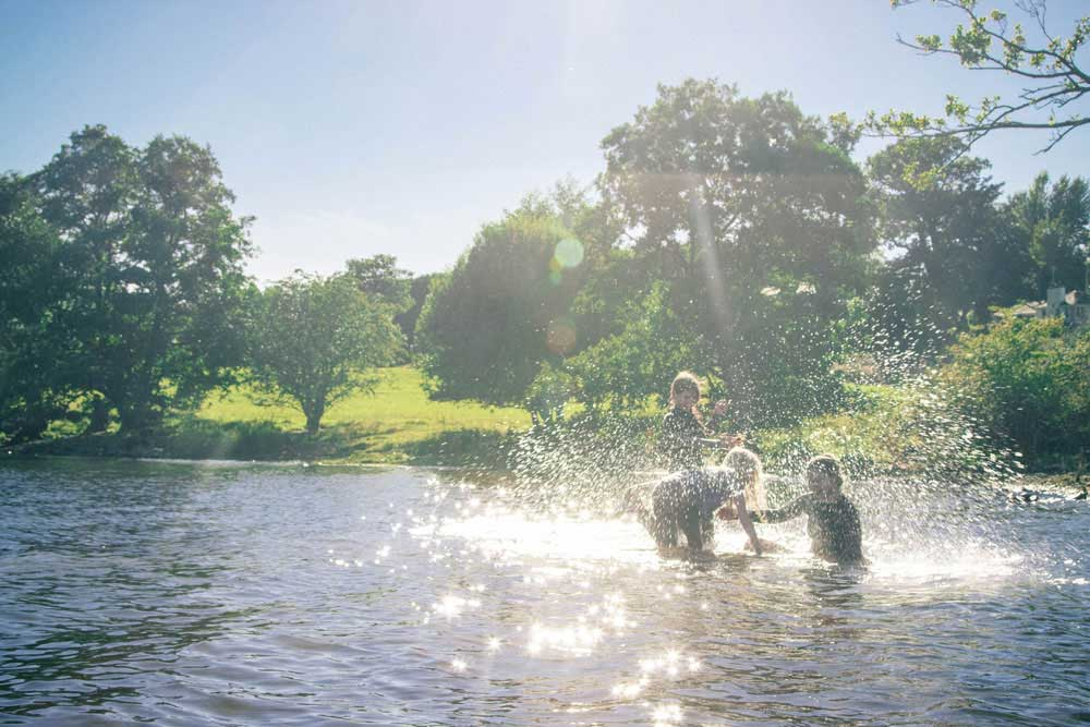 Kids splashing and playing in Ullswater during their stay at Another Place - a new hotel in the Lake District