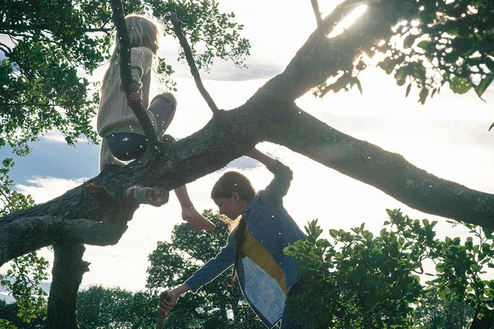 Two young girls tree climbing at Another Place, a hotel in the Lake District