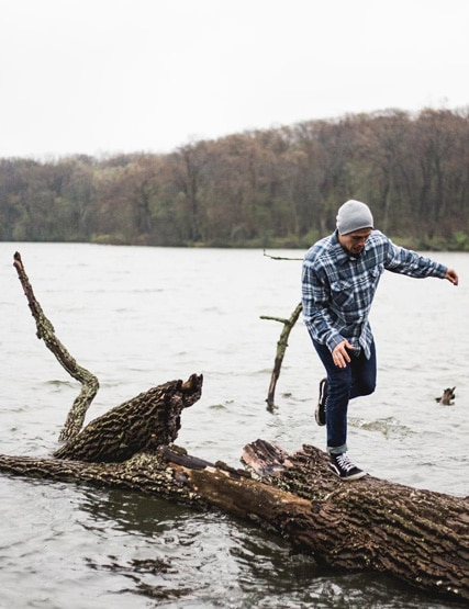 Young man walking on logs on the lake shore