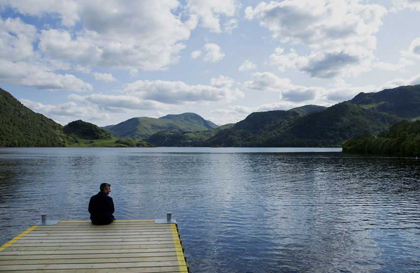 Man sitting on the jetty at Aira Force on Ullswater