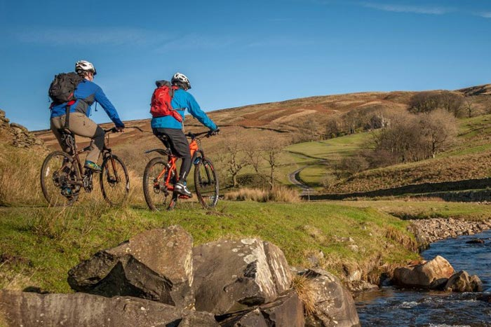 Two cyclists mountain biking in the Lake District. Photo: Cumbria Tourism Library