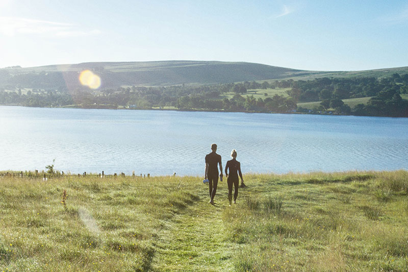 Couple walking down to Ullswater for an early morning swim during their stay at Another Place, The Lake.
