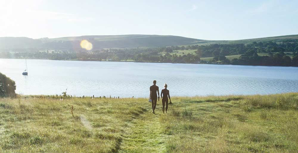 A couple walking down to Ullswater's shore for an early morning swim