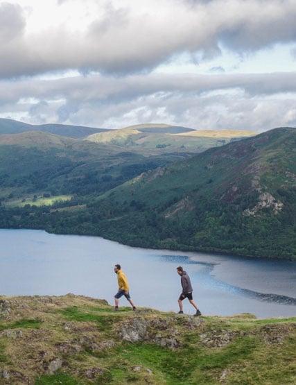 Two friends walking on Hallin Fell overlooking Ullswater