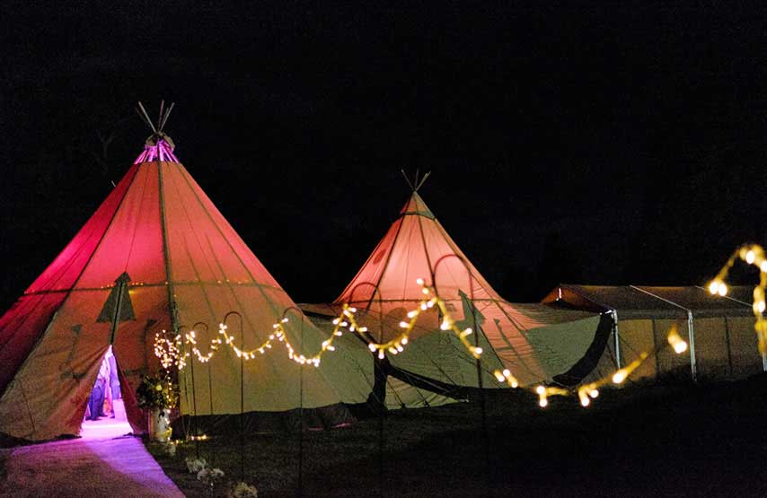 Tipi lit up at night for an evening wedding reception at Another Place, The Lake