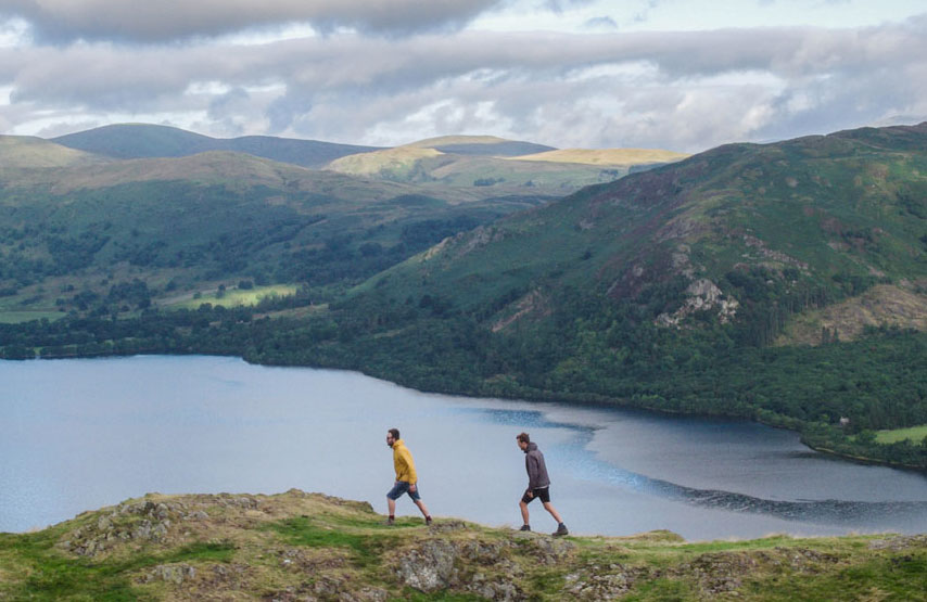 Two friends walking on Hallin Fell and taking in the awesome views of Ullswater in the Lake District