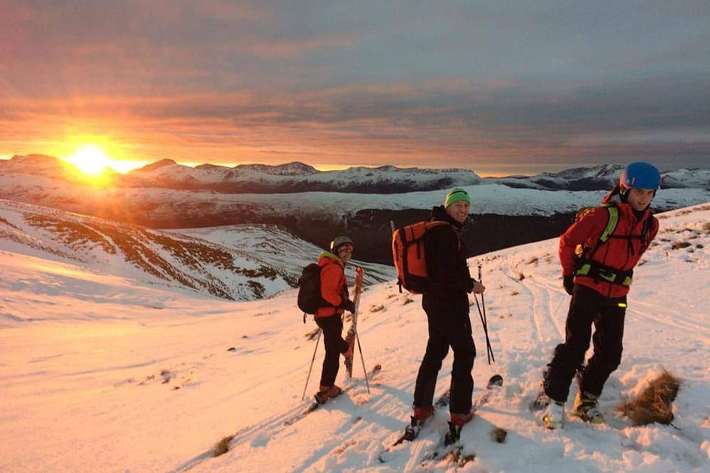 Skiers making their way down Raise at sunset in the Lake District