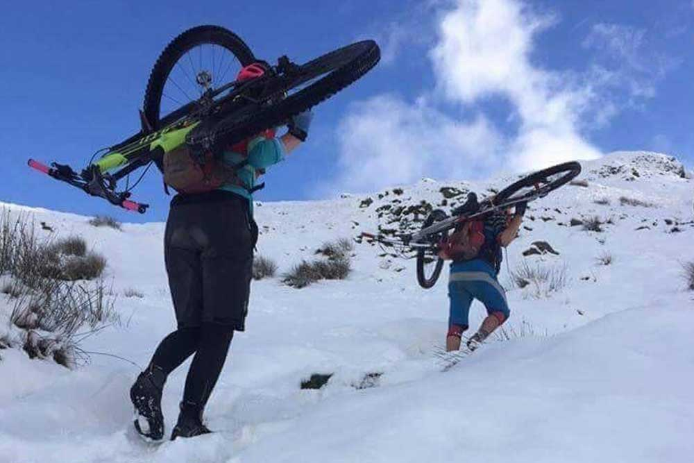 Carrying mountain bikes up a snow-covered fell in the Lake District