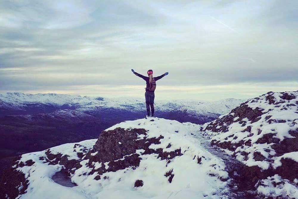 Standing on top of a snow-covered fell in the Lake District