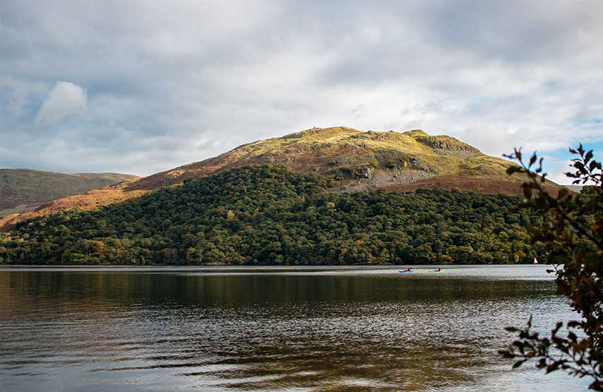 Kayakers on Ullswater with the autumnal landscape behind them