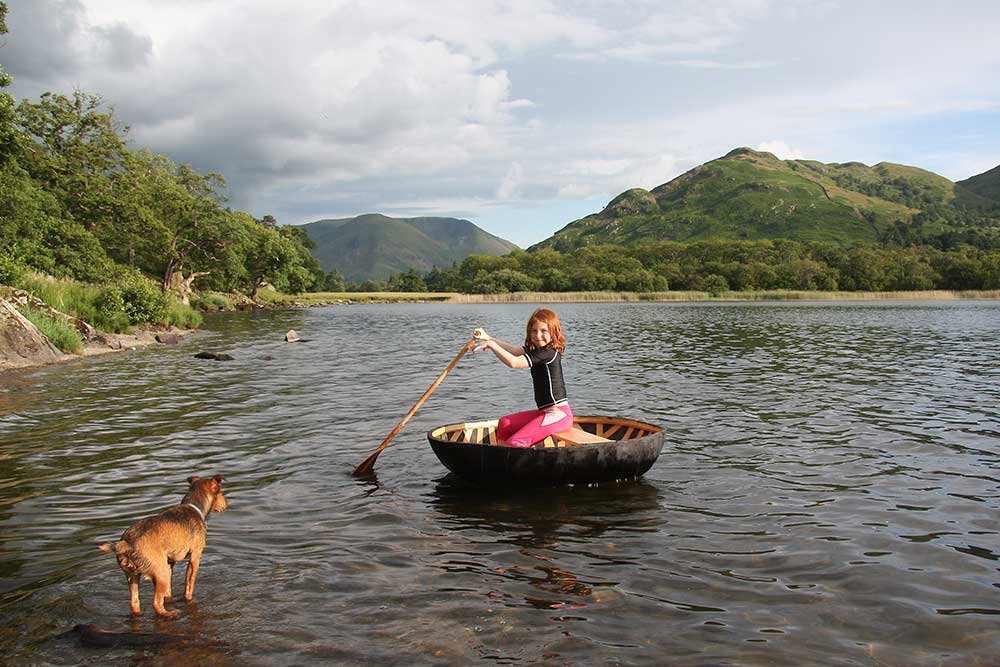 Young girl playing with her dog in Ullswater in the Lake District