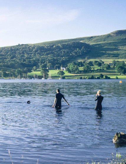 Young couple walking into the lake for a swim