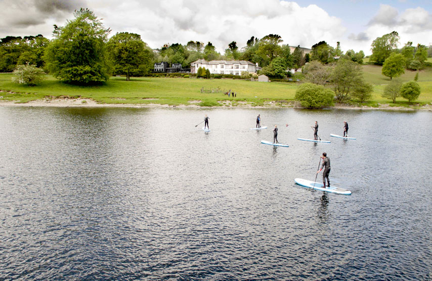 Group of people stand up paddle boarding on Ullswater