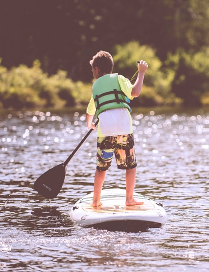 A young boy stand up paddling on Ullswater