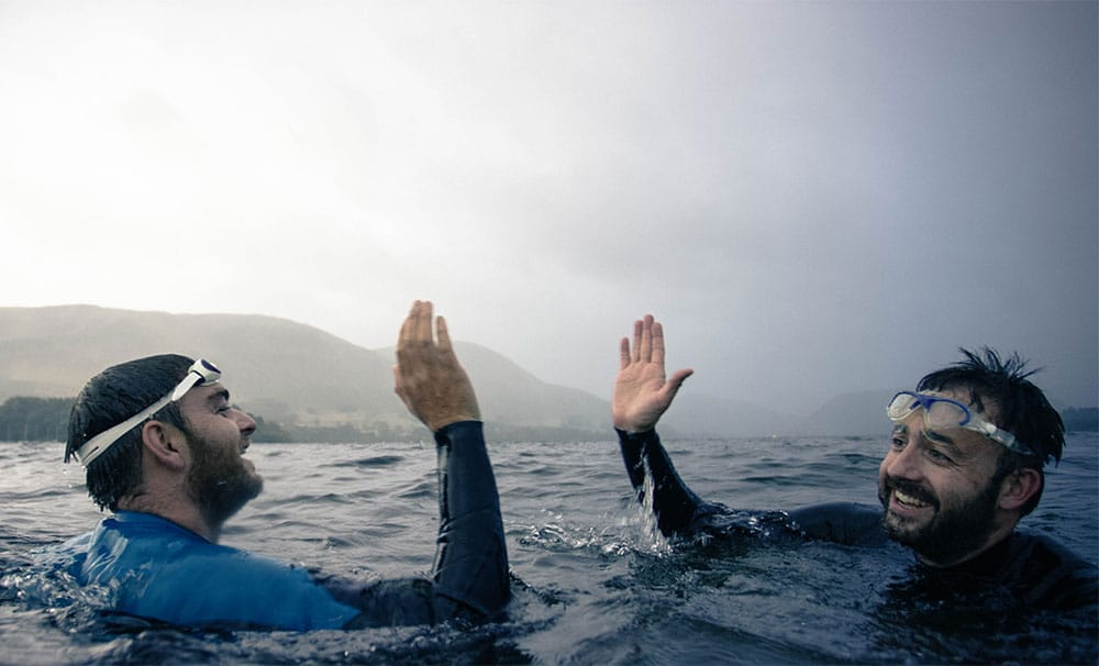 Two friends high five after a wild swim in Ullswater