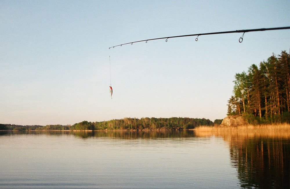 A fishing rod being cast into the lake