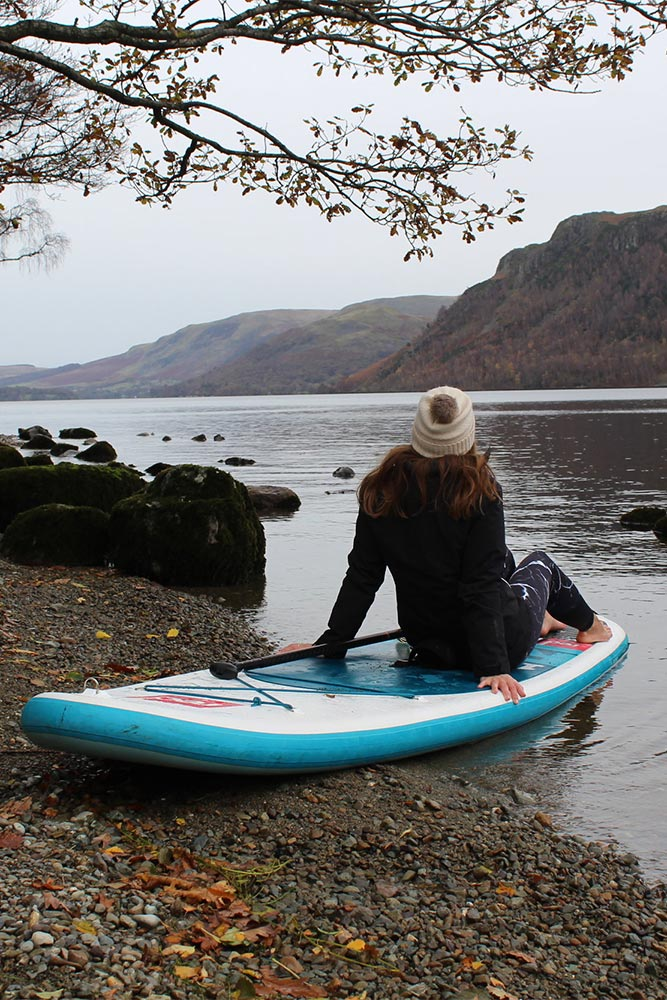 Woman sitting on a SUP by the lake