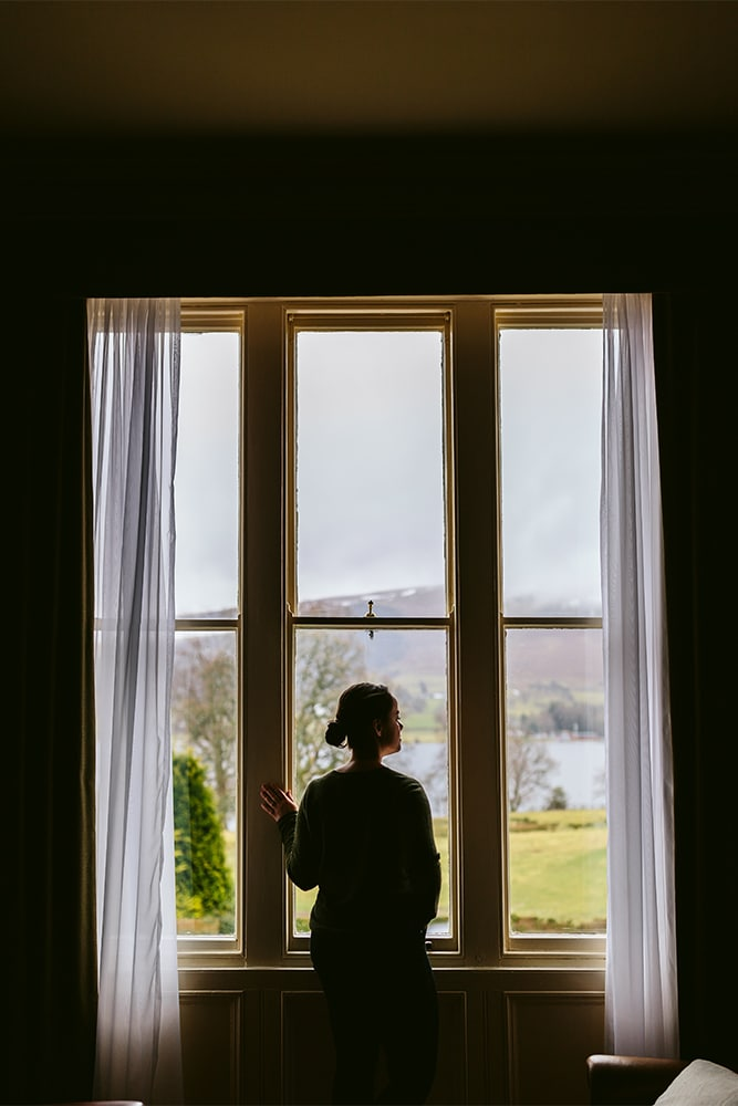 Woman standing by a window looking out at the Lake District
