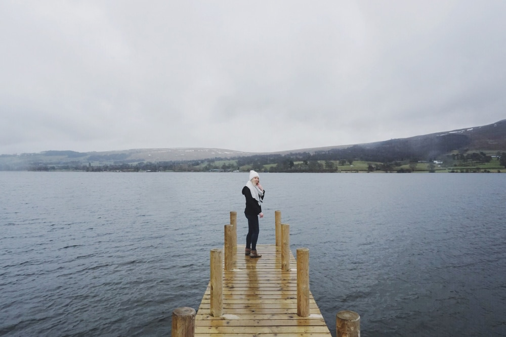 Woman standing on a jetty in the Lake District