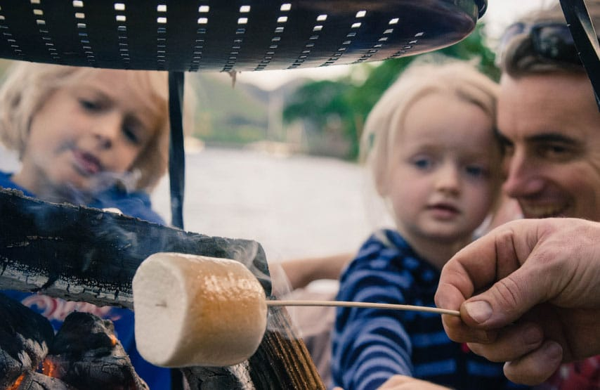 A family toasting marshmallows over a fire