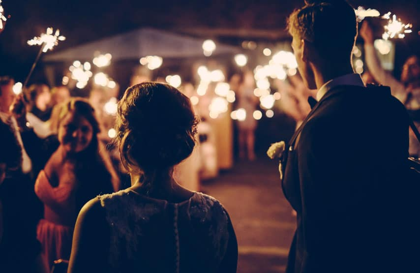 Wedding couple walking through friends holding sparklers